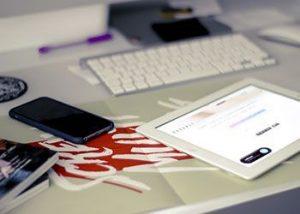 iPad encendido, smartphone y teclado de ordenador sobre un escritorio