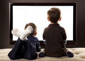 Dos niños mirando la tv en una postura incorrecta