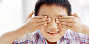Niño tapándose los ojos y sonriendo