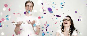 Chica y chico con gafas graduadas jugando con confetti y sonriendo