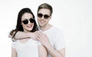 Chica y chico con gafas de sol y sonriendo.