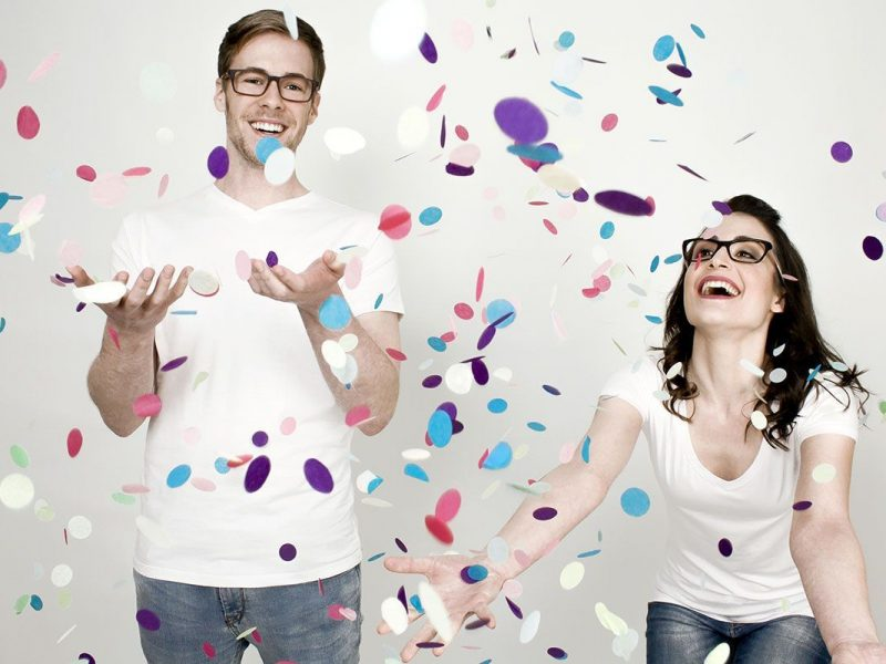 Chica y chico con gafas graduadas y jugando con confetti