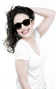Chica sonriendo con gafa de sol de A Óptica de Ana