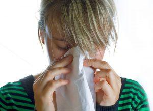Mujer sonándose la nariz.