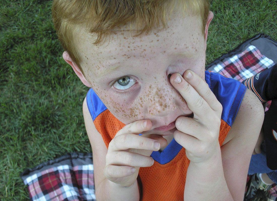 Niño frotándose un ojo.